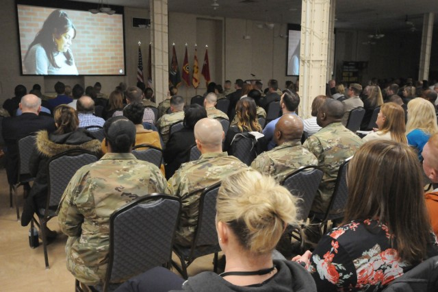 Soldiers, Army civilians and representatives of local agencies watch a video representing survivors of sexual assault, during the National Sexual Assault Awareness and Prevention Month Kick off, April 2 at Heritage Hall, Rock Island Arsenal, Illinois.