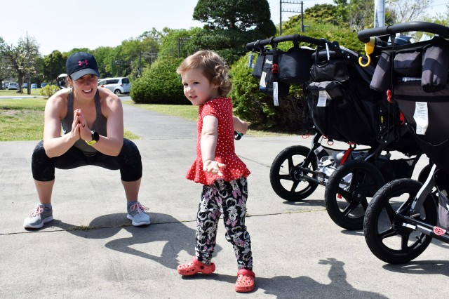 Melissa Aurich, a coordinator of the Camp Zama Stroller Warriors, does strength training with her daughter Lincoln, 2, in front of the U.S. Army Japan Headquarters at Camp Zama April 23.