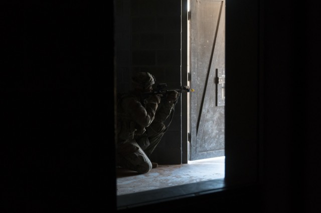 A Soldier with Company C, 1st Battalion, 37th Armored Regiment, 2nd Brigade Combat Team, 1st Armored Division, pulls security during an assault on a mock village, April 8 at Orogrande, New Mexico. The infantryman exposes just enough of his body, so he can identify anyone trying to enter the building. (U.S. Army photo by Sgt. Brandon Banzhaf, 24th Theater Public Affairs Support Element)