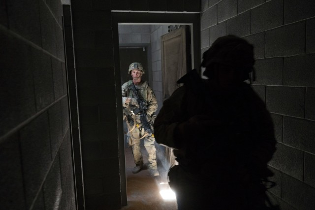 A pair of Soldiers with Company C, 1st Battalion, 37th Armored Division, 2nd Brigade Combat Team, 1st Armored Division flow through a hallway, clearing rooms, as they progress through the building, April 8 at Orogrande, New Mexico. Squads of infantrymen had to assault the mock village and overcome the opposing force. (U.S. Army photo by Sgt. Brandon Banzhaf, 24th Theater Public Affairs Support Element)