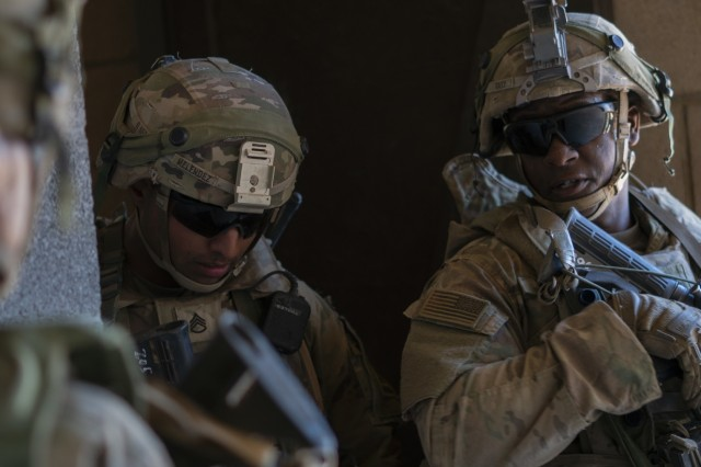 Sgt. Jordan Gary (right), a Merced, California native and infantryman with Company C, 1st Battalion, 37th Armored Regiment, 2nd Brigade Combat Team, 1st Armored Division, provides his squad leader a situation report of his team. Gary had to maneuver his team through certain buildings and adapt with the company as the battlefield changed. (U.S. Army photo by Sgt. Brandon Banzhaf, 24th Theater Public Affairs Support Element)