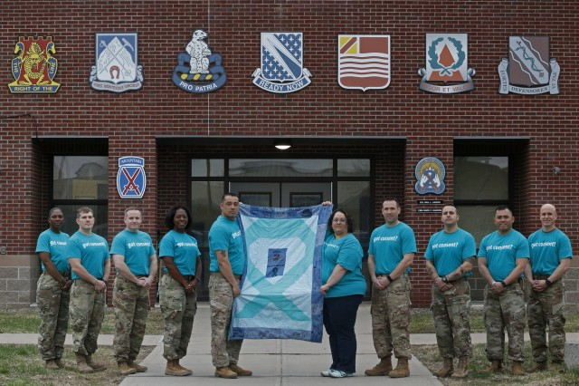 "Leaders from battalions across 2nd Brigade Combat Team, 10th Mountain Division, joined Sgt. 1st Jorge Class De Alba (center left), and Nicole Bellinger (center right), of the 2BCT Sexual Harassment/Assault Response and Prevention team for a group photo commemorating Denim Day during Sexual Assault Awareness and Prevention Month, April 24, 2019, at Fort Drum, New York. Josiphina Nelson, a volunteer, sewed the 2BCT SHARP team's ""inspiration quilt"" in recognition of Denim Day and the message of consent. Commando Soldiers and Family members designed the denim squares with supportive messages and words of encouragement for survivors of sexual violence. (U.S. Army photo illustration by Staff Sgt. Paige Behringer)"