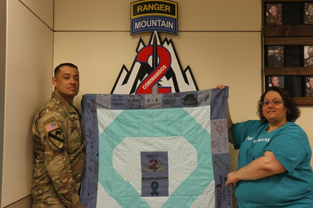 "Sgt. 1st Jorge Class De Alba (left), and Nicole Bellinger, of the 2nd Brigade Combat Team, 10th Mountain Division Sexual Harassment/Assault Response and Prevention team, pose for a photo holding a denim quilt to commemorate Denim Day during Sexual Assault Awareness and Prevention Month, April 24, 2019, at Fort Drum, New York. Josiphina Nelson, a volunteer, sewed the 2BCT SHARP team's ""inspiration quilt"" in recognition of Denim Day and the message of consent. Commando Soldiers and Family members designed the denim squares with supportive messages and words of encouragement for survivors of sexual violence. (U.S. Army photo by Staff Sgt. Paige Behringer)"
