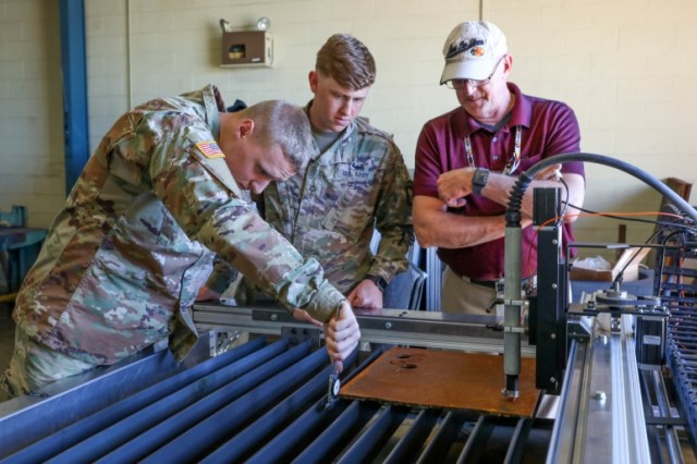 Soldiers of the 584th Maintenance Company, 129th Combat Sustainment Support Battalion, 101st Sustainment Brigade, 101st Airborne Division (Air Assault),  measure the thickness of a piece of sheet metal, while civilian engineering instructors demonstrate how to use the plasma cutter machine. The plasma cutter is one of many pieces of equipment housed within the Metal Working and Machining Shop Set (MWMSS) given to the 584th MC, who base their operations out of Fort Campbell, Kentucky, April 3-12, 2019. The 584th MC will be the first company within the 101st Abn. Div. to receive this new and innovative equipment. (U.S. Army photo by Staff Sgt. Caitlyn Byrne, 101st Sustainment Brigade Public Affairs)