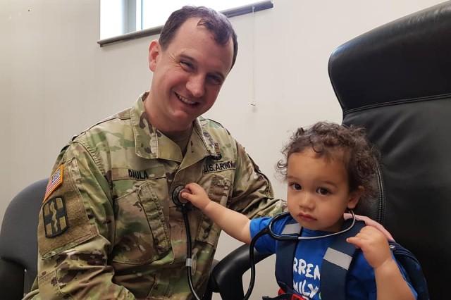 Calvin Daula, son of Maj. John Daula, Army psychiatrist, checks his dad's heartbeat with a stethoscope.