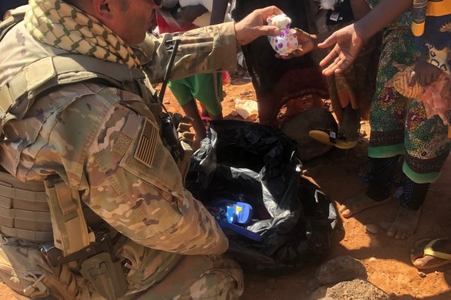 Sgt. 1st Class Robert Rodriguez, a platoon sergeant for the 1st Battalion, 141st Infantry Regiment, 72nd Infantry Brigade Combat Team, 36th Infantry Division of the Texas Army National Guard, hands out a stuffed animal to a young child, February 2019 in Djibouti. Rodriguez gifted 500 sandals to barefoot orphans and children during their deployment. Rodriguez coordinated the sandal donation effort with his daughter's school, The Blessed Sacrament in Laredo, Texas. Rodriguez, who has been a part of the Texas National Guard Joint Counterdrug Task Force for 18 years, is no stranger to building local and national partnerships. Task force members build strong relationships with law enforcement partners and community based organizations in their local communities in an effort to combat drug related threats.