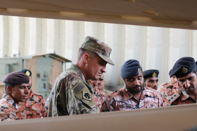 U.S. Army Sgt. 1st Class Chad Collins and Royal Army of Oman Soldiers inspect a tire after removing rim cover during the Heavy Equipment Transporter System Subject Matter Exchange II held at Sultan bin Safy Camp Shafa Oman, April 6-11, 2019. (U.S. Army photo by Sgt. Nahjier Williams)