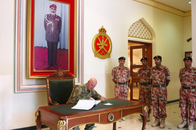 U.S. Army Col. Rodney Honeycutt, 1st TheaterbSustainment Command deputy commanding officer, signs the Royal Army of Oman's guess book following the Heavy Equipment Transporter System Subject Matter Exchange II held at Sultan bin Safy Camp Shafa Oman, April 6-11, 2019. (U.S. Army photo by Sgt. Nahjier Williams)