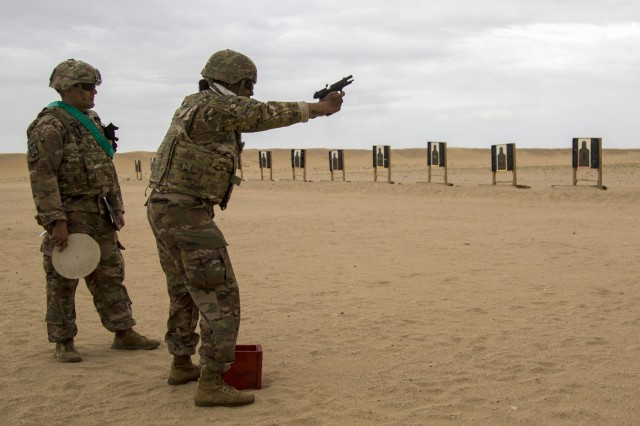 CAMP ARIFJAN, Kuwait - Army Sgt. Tadalies Sanchez, 637th Chemical, Biological, Radiological and Nuclear Company, shoots at targets while her grader, Staff Sgt. Jonathan White, 300th Sustainment Brigade, looks on during the range qualification event of the German Armed Forces Badge (GAFB) for Military Proficiency on April 9, 2019, at Udairi Range, Kuwait. During this event, participants stand and shoot a total of five rounds with a Beretta M9 at three silhouettes. Participants, who must hit each target at a minimum, shoot in order at targets one, two, three, one, two and earn bronze with three hits, silver for four hits and gold for five hits. U.S. Army Central hosts events such as the GAFB to enhance service member's personal abilities to stay combat ready which improves overall capabilities. (U.S. Army Reserve photo by Sgt. Christopher Lindborg, U.S. Army Central Public Affairs Office)