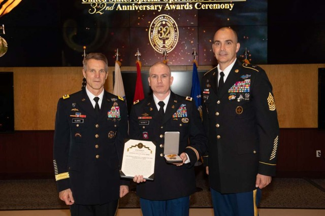 Colonel Charles R, Burnett, Commander, 95th Civil Affairs Brigade, accepts the presentation pieces for Colonel Charles R. Munske from USSOCOM commander General Richard D. Clark and USSOCOM Command Sergeant Major Patrick L. McCauley, April 18, 2019.