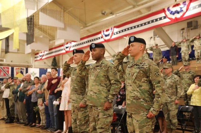 Command Sgt. Maj. Charles W. Tennant, Col. Monte Rone and Command Sgt. Maj. Delfin J. Romani, 1st Stryker Brigade Combat Team, 4th Infantry Division salute the flag during the change of responsibility