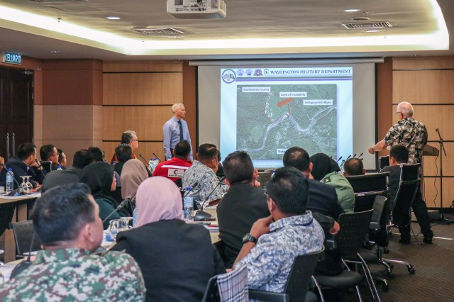 U.S. Army Lt. Col. Jonathan Steinbach from the Washington Army National Guard and Chris Utzinger, response section manager for the Washington Military Department Emergency Management Division delivers a presentation in front of nearly 50 stakeholders from natural disaster response agencies in the Indo-Asia-Pacific during the first Malaysian Civil-Military Coordination on Humanitarian and Disaster Relief Course, at the Malaysian Armed Forces Officer Mess, Wisma Perwira, in Kuala Lumpur, Malaysia, April 18, 2019. The course is designed to enhance the knowledge of disaster response stakeholders in Malaysia and operationalize civil-military coordination at the national, regional and international levels.