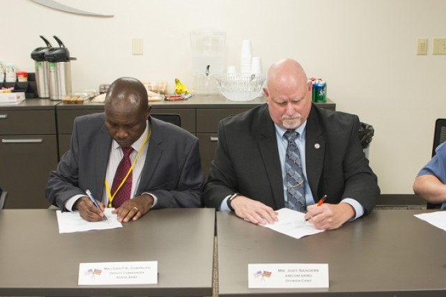 Senior members of the U.S. and Kenyan MD-530F delegation sign the summary and minutes after the Kenyan MD-530F Program Management Review, April 8-9 in Huntsville. Seated on left is Marine Corps Maj. Jason Moore, security cooperation officer at U.S. Embassy in Kenya, and Maj. Gen. Thomas Chepkuto, deputy commander of Kenyan Army. On right is Jody Sanders, chief of Non-standard Aviation at Aviation and Missile Command, and Bill Kaundart, country program manager for Kenya, from the Security Assistance Command. Signing the minutes is a formal acknowledgement that all parties agree with the review and the action items identified to be worked. The MD-530F is a light scout and attack helicopter that is scheduled to start being delivered to Kenya in May.