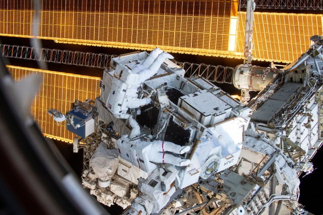 Astronaut Lt. Col. Anne McClain, wearing the spacesuit with red stripes, and Air Force Col. Nick Hague work to retrieve batteries and adapter plates from an external pallet during a spacewalk to upgrade the International Space Station's power storage capacity March 22, 2019. McClain, one of five Soldiers in the Army Space and Missile Defense Command's astronaut detachment, is currently on a six-month mission in space.