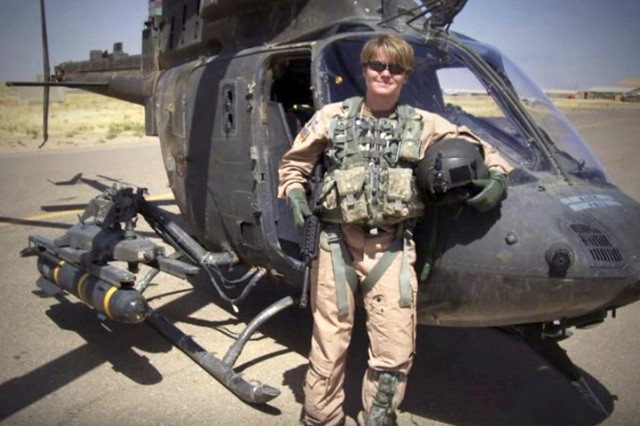 Anne McClain, now an astronaut and lieutenant colonel, stands next to a OH-58 Kiowa helicopter. Before becoming an astronaut, McClain flew over 200 combat missions and served as a Kiowa instructor pilot. She is now one of five Soldiers in the Army Space and Missile Defense Command's astronaut detachment and is currently on a six-month mission in space.