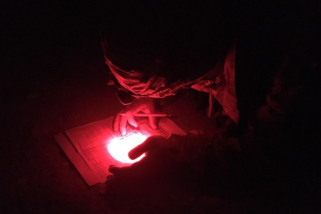 FORT CARSON, Colo. -- Candidate Staff Sgt. Josejaime Santoslopez, a combat medic from Charlie Company, 4th Brigade Support Battalion, 1st Stryker Brigade Combat Team, 4th Infantry Division, plots his points during night land navigation testing at Fort Carson, Colo., Apr. 15, 2019.