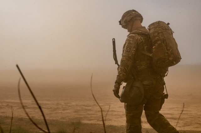 Lt. Col. Andrew Hercik, left, Commander of 1st Battalion, 14th Field Artillery Brigade, 75th Field Artillery Brigade, Fort Sill, Okla., walks through the cloud of dust produced from an Air Force C-130J Super Hercules taking off at Fort Chaffee, Ark., during Operation Phantom Flight on April 12, 2019. Operation Phantom Flight is a joint service operation where both Soldier and Airmen worked alongside one another to successfully mobilize and transport Steel Warrior Battalions HIMARS from Henry Post Army Airfield, Okla., to Fort Chaffee, Ark., in order to successfully conduct an air/land raid.