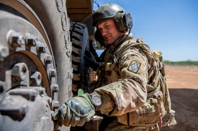 Spc. Daniel Brooks, a crewmember assigned to 1st Battalion, 14th Field Artillery Brigade, 75th Field Artillery Brigade, Fort Sill, Okla., checks the tire pressure of the M142 HIMARS prior to loading it into an Air Force C-130J Super Hercules at Fort Chaffee, Ark. during Operation Phantom Flight, April 12, 2019. Operation Phantom Flight is a joint service operation where both Soldier and Airmen worked alongside one another to successfully mobilize and transport Steel Warrior Battalions HIMARS from Henry Post Army Airfield, Okla., to Fort Chaffee, Ark., in order to successfully conduct an air/land raid.