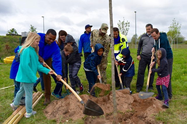 Children and adult community members plant fruit trees together on Arbor Day at USAG Ansbach, April 26, 2019.
