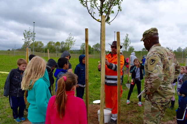 Roland Krug, USAG Ansbach's arborist, explains tree care to children and Command Sgt. Maj. Philson Tavernier on Arbor Day at USAG Ansbach, April 26, 2019.
