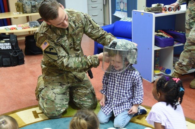 In celebration of Month of the Military Child, military policemen assigned to U.S. Army Garrison Benelux, talked to children about what it is like to be a military policeman during a special visit to the Child Development Center in Brussels, April 17, 2019. The military policemen wanted to educate children on how the police keep the community safe by letting them try on their gear.