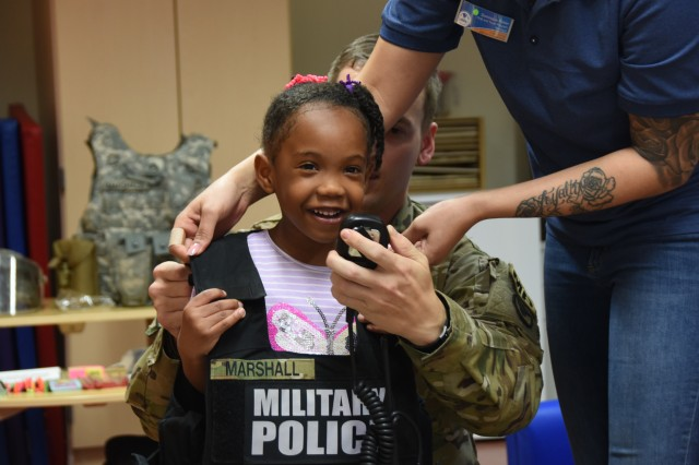 In celebration of Month of the Military Child, military policemen assigned to U.S. Army Garrison Benelux, talked to children about what it is like to be a military policeman during a special visit to the Child Development Center in Brussels, April 17, 2019. During the event, children got the opportunity to try wear police gear and speak into their radio.
