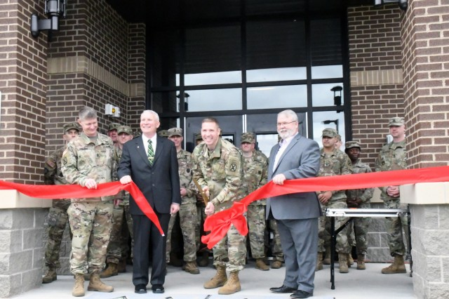 10th Mountain Division (LI) and Fort Drum senior leaders and invited guests toured the new Noncommissioned Officer Academy following a ribbon cutting ceremony April 25. Pictured, from left, are Command Sgt. Maj. Samuel Roark, 10th Mountain Division (LI) and Fort Drum senior enlisted adviser; retired Command Sgt. Maj. Joe McLaughlin, former NCOA commandant; Command Sgt. Maj. Jeffrey Loehr, NCOA commandant; and retired Command Sgt. Maj. Jim Boschette, former NCOA commandant.The two-floor, 40,000 square foot building includes eight classrooms -- each can seat 20 students -- an 8,000 square foot indoor training facility, an auditorium that seats up to 206 occupants, a learning and resource center, barracks and an outdoor track. The next Basic Leader Course class will begin training at the new facility on April 29. (Photo by Mike Strasser, Fort Drum Garrison Public Affairs)