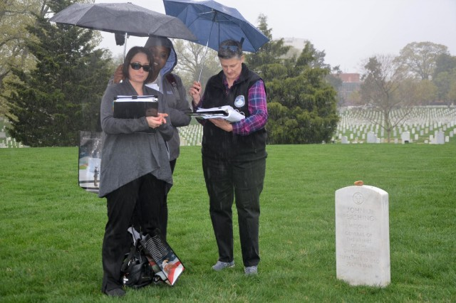 Melissa Olivas, from the Security Assistance Command's New Cumberland, Pa., location, provides an overview about Gen. John J. Pershing during a Mentor Program staff ride to Arlington National Cemetery. Daveine Butler and Ann Scott, also from New Cumberland, assist with umbrellas.