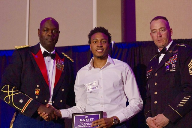 "Lt. Col. Reginald White and Command Sgt. Maj. Michael Deatherage both from the 1st Battalion, 7th Field Artillery Regiment, 2nd Armored Brigade Combat Team, 1st Infantry Division, award Kamu Stokes of the Kansas State University Men's Basketball Team the ""Never Broken"" Award at the annual team banquet, April 11."