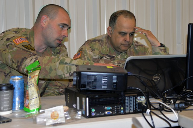 Chief Warrant Officer 2 Brian Gosch (left) off Milton, Washington, points out a network abnormality to Capt. Sameer Puri of Federal Way, Washington, during Cyber Shield 19 at Camp Atterbury, Ind., from April 5-19, 2019. Both Soldiers are members of the Washington National Guard's Cyber Mission Assurance Team.