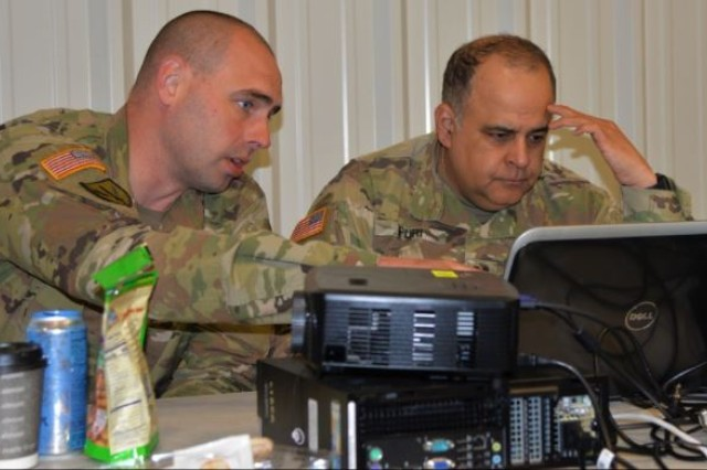 Chief Warrant Officer 2 Brian Gosch, left, of Milton, Wash., points out a network abnormality to Capt. Sameer Puri of Federal Way, Wash. during Cyber Shield 19 at Camp Atterbury, Ind., from April 5-19, 2019. Both Soldiers are members of the Washington National Guard's Cyber Mission Assurance Team.