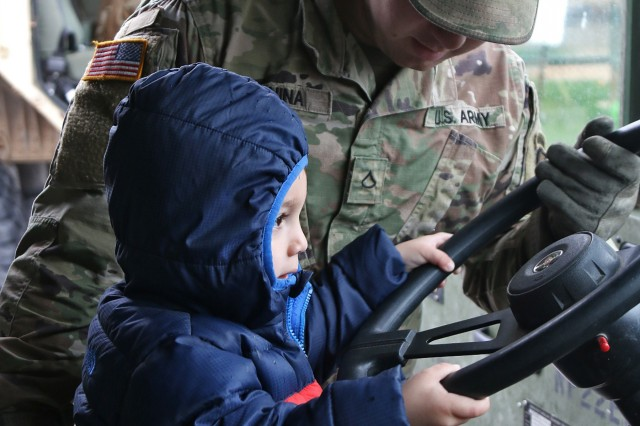 Pfc. Joseph Manina, a heavy machinery operator assigned to E Company, 41st Engineer Battalion, 2nd Brigade Combat Team, 10th Mountain Division, teaches preschool children about military vehicles during during a static display at Memorial Child Development Center in honor of Month of the Military Child, April 26, 2019, at Fort Drum, New York. Mountain Sappers discussed their duties and explained safety while showing toddlers and kindergarteners two Heavy Expanded Mobility Tactical Trucks. (U.S. Army photo by Staff Sgt. Paige Behringer)