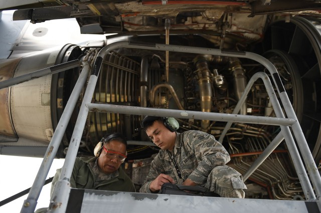 Master Sgt. Ruel Lechadores, left, 446th Aircraft Maintenance Squadron crew chief, and Airman 1st Class Ryan Watts, 62nd Aircraft Maintenance Squadron crew chief, communicate and work to repair an engine on a C-17 Globemaster III April 3 on March Air Reserve Base, Calif.