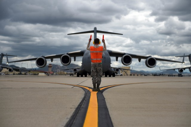 Senior Airman Nathan Cremeans, 62nd Aircraft Maintenance Squadron crew chief, marshals a C-17 Globemaster III as it prepares to take off from March Air Reserve Base, Calif., April 3.