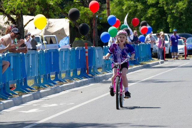 A competitor rides her way across the finish line after a 1 kilometer cycling event during the 2015 Special Olympics Washington at Joint Base Lewis-McChord, Wash., May 30.