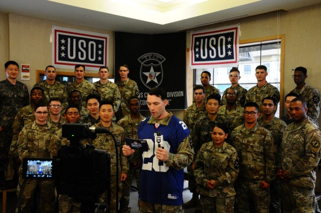 CAMP HUMPHREYS, Republic of Korea - Warrant Officer James Benecke, chemical, biological, radiological, nuclear technician, Brooklyn, New York native, reads the New York Giants' 17th draft pick during a live broadcast at the One-Stop USO, April 26.