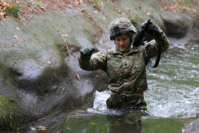 U.S. Army Reserve Spc. Kathryn Hubble, a combat medic healthcare specialist with the 209th Digital Liaison Detachment, 7th Mission Support Command (MSC), Wiesbaden, Germany, wades through a trench while maneuvering the obstacle course during the 7th MSC Best Warrior Competition (BWC) in Kaiserslautern, Germany, April 26, 2019. BWC is an annual event designed to test the physical fitness, military knowledge, marksmanship, endurance and land navigational skills of each competitor. (U.S. Army Reserve photo by Sgt. Christopher Stelter, 221st Public Affairs Detachment)