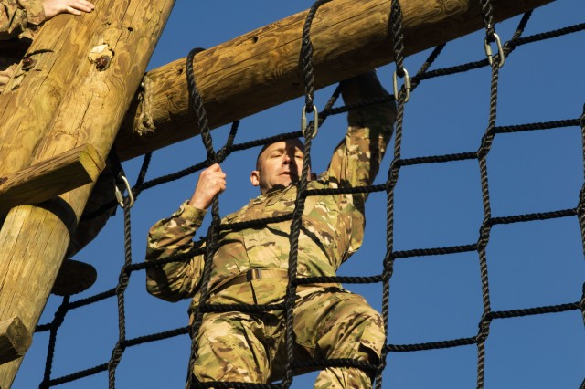 Staff Sgt. Joseph Polsca, with the 261st Multi-Functional Medical Battalion, 44th Medical Brigade, maneuvers over a roped net obstacle during the Operation Dragon Medic Strong competition at the Deglopper Air Assault Obstacle Course, Fort Bragg, N.C., April 16, 2019. Operation Dragon Medic Strong is a three-day competition designed to be physically, mentally and spiritually challenging. (U.S. Army photo by Spc. ShaTyra Reed / 22nd Mobile Public Affairs Detachment)