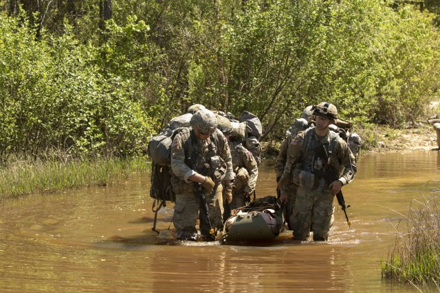 Members of Team C, with the 261st Multi-Functional Medical Battalion, 44th Medical Brigade, navigate through knee-high creek water with a simulated casualty during the Operation Dragon Medic Strong's Warrior Tasks and Battle Drills lanes at Fort Bragg, N.C., April 16, 2019. The goal of the lanes training was to treat and evacuate simulated casualties across a mapped area. (U.S. Army photo by Spc. ShaTyra Reed / 22nd Mobile Public Affairs Detachment)