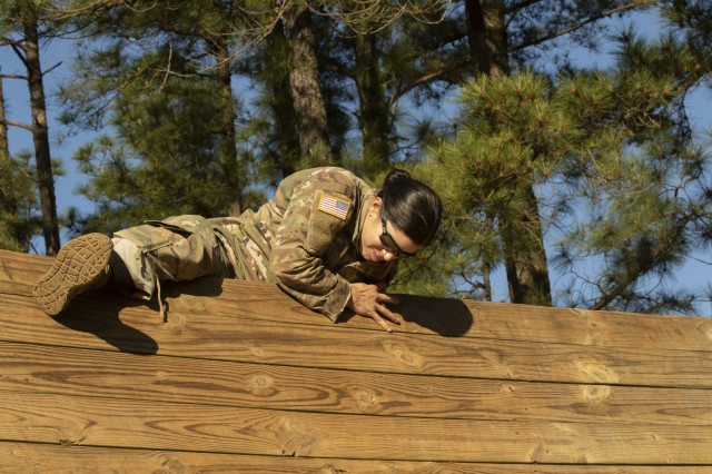 Capt. Tara Trojanello, with the 28th Combat Support Hospital, 44th Medical Brigade, successfully climbs over a wall as part of the obstacle course event during the Operation Dragon Medic Strong competition at Deglopper Air Assault Obstacle Course, Fort Bragg, N.C., April 16, 2019. The course was comprised of obstacles designed to help build confidence by overcoming physical challenges. (U.S. Army photo by Spc. ShaTyra Reed / 22nd Mobile Public Affairs Detachment)