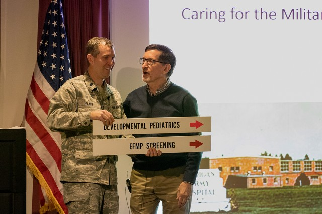Dr. Glenn Tripp, who completed a fellowship during the earliest years of the Developmental-Behavioral Pediatrics Fellowship Program at Madigan Army Medical Center, presented the original hallway sign to the current director, Lt. Col. (Dr.) Eric Flake at the Caring for the Military Child Symposium at Madigan Army Medical Center on Apr. 18.