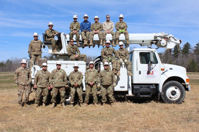 Power Distribution Specialists in the 249th Engineer Battalion pose with one of their utility trucks after the completion of a power distribution system during a field training exercise at Fort AP Hill, Virginia. The soldiers and reservists assigned to this battalion complete a mission unlike anything found elsewhere in the Army by providing commercial-level power to military units and federal relief organizations.