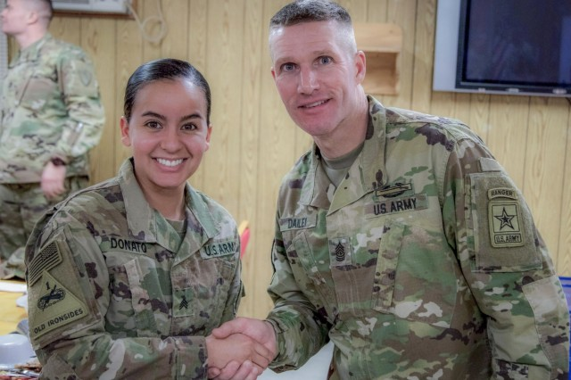 Sgt. Von Marie Donato, a public affairs non-commissioned officer assigned to Combined Joint Forces Land Component Command - Operation Inherent Resolve and 1st Armored Division, shakes hands with Sergeant Maj. of the Army Daniel A. Dailey, during his visit to Baghdad, Iraq, Dec. 18, 2017, to discuss leader development initiatives, talk to the troops and enjoy a holiday meal with Soldiers. (U.S. Army photo by Spc. Avery Howard)