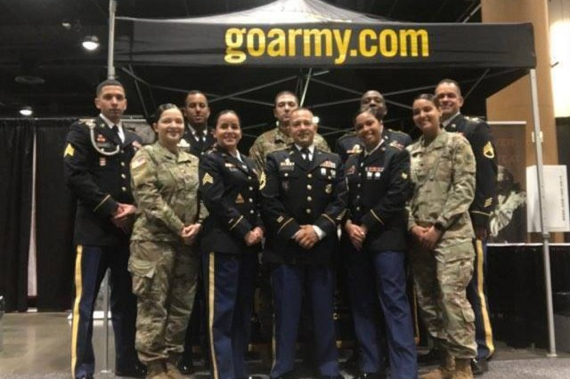 (Pictured Center) Sgt. 1st Class Leonel Castillo, a U.S. Army recruiter with the Kissimmee Recruiting Office, Tampa Recruiting Battalion, 2nd Recruiting Brigade, United States Recruiting Command, and (pictured left of Castillo) Sgt. Von Marie Donato, a Special Recruiter Assistance Program participant and a public affairs specialist assigned to U.S. Army Central, pose for a group photo along with other SRAP participants at the Tom Joyner Family Reunion Convention Show in Orlando, FL at the Gaylord Palms Resort Aug. 31, 2017. (U.S. Army photo courtesy of Tampa Recruiting Battalion)