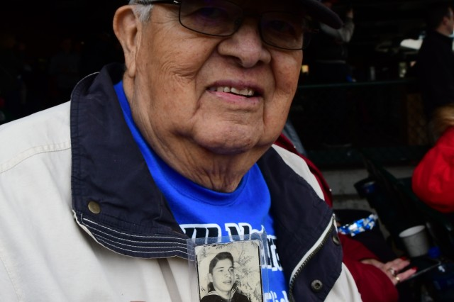 Pedro Carrillo, a 92-year-old World War II and Korean War veteran, holds up a picture of his younger self in 1943, when as a 17-year-old sailor he attended basic training prior to sailing to the Pacific Theater to battle Japanese forces. He enjoyed the military appreciation game with members of his family.