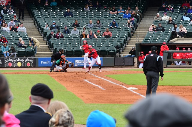 A Soldier in his Class A military uniform (bottom left) watches the Louisville Bats game with his family.