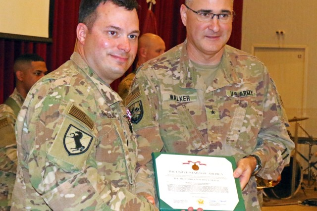 Lt. Col. Leo Karanikolas, 420th Transportation Battalion, receives the Meritorious Service Medal from Brig. Gen. Clint E. Walker, commanding general of 184th Sustainment Command, during a transfer of authority ceremony at Camp Arifjan, Kuwait, April 25, 2019. The Sherman Oaks, Calif. based 420th officially transfers authority of the theater movement control battalion mission to the Manhattan, Kan. based 450th Transportation Battalion on April 28, 2019.