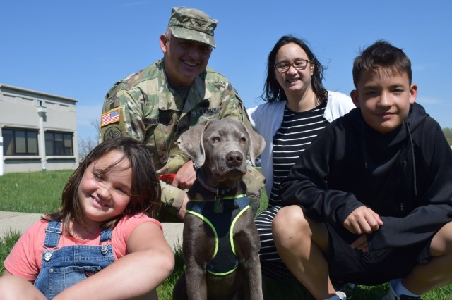 Col. Michael Garlington, commander of Crane Army Ammunition Activity, with his wife Kim and their children Kayleigh and Aidan with their dog Murphy on the lawn at Crane Army. Kayleigh and Aidan, like other sons and daughters of American service members, make significant sacrifices including frequent moves during their father's military career. Crane Army Ammunition Activity produces and provides conventional munitions requirements in support of U.S. Army and Joint Force readiness. It is one of 14 installations of the Joint Munitions Command and one of 23 organic industrial base installations under the U.S. Army Materiel Command, which include arsenals, depots, activities and ammunition plants.
