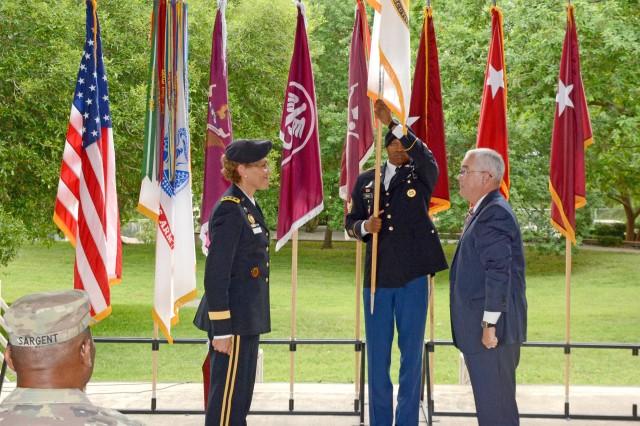 Command Sergeant Major Michael L. Gragg, MEDCOM Command Sergeant Major, unfurls the SES flag as Lt. Gen. Nadja Y. West and Joseph M. Harmon III look on.