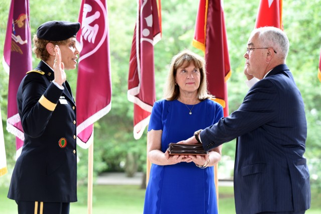 Lt. Gen. Nadja Y. West administers the oath of office to Joseph M. Harmon III as his with Alice looks on.